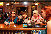 Roller girls talk with the bartender at Barton Springs Saloon in Austin, Texas, after a bout between the Hellcats and Putas del Fuego.