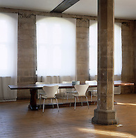 In this conversion of an 1820s church a dining area has been created with a long wooden refectory table and Arne Jacobsen chairs