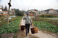 A man carrying sewage from outhouses walks among small farm patches in an old-style residential area in the outskirts of Nanjing, Jiangsu, China.
