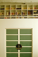 A double door of green glass with chrome handles leads to a mezzaine office with custom-built bookshelves lining the walls