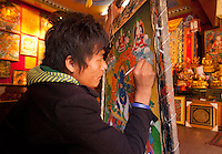 A young Tibetan artisan paints a Thangka, a traditional often very colorful depiction of Buddhist deities or historical scene