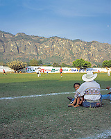 Tepotzlan, Morelos, Mexico, March 20, 2006. A man and his daughter watch as two girls teams play a football match at the foot of the Tepotzteco mountains. Fever for the 2006 world cup approaches its peak
