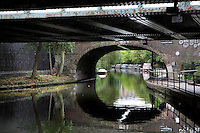 Regent's Canal beneath the Gloucester Avenue bridge and a railway bridge, London, UK. Regent's Canal links the Paddington arm of the Grand Union Canal; just north-west of Paddington Basin in the west; to the Limehouse Basin and the River Thames in east London. It was built by John Nash (architect) and James Morgan (engineer) and opened in two stages, from Paddington to Camden in 1816, and the rest of the canal in 1820. Picture by Manuel Cohen