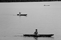 Indigenous kids paddle in their one-person dugout canoe on the Amazon river, Amazonia, Brazil, 6 March 2004. Amazonia is the world's largest dense tropical forest area. Since the 16th century the original indigenous people have been virtually pushed away or exterminated. The primal ancient unity between tribes and the jungle ambient has changed into a fight between the urban based civilization and the jungle enviroment. Although new generations of white and mestizo settlers have not become adapted to the wild tropical climate and rough conditions, they keep moving deeper into the virgin forest. The technological expansion causes that Amazonia is changing rapidly.