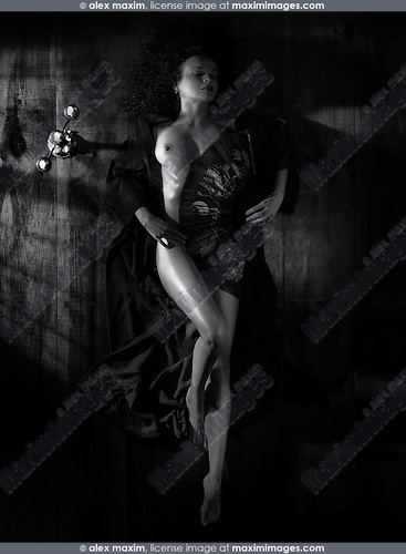 Beautiful naked woman in kimono lying on the floor in dim dramatic light covering her nude body with an asian fan view from above Black and white