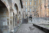 Cloister colonnade with the main building of the Abbatiale Sainte-Foy de Conques or Abbey-church of Saint-Foy behind, Conques, Aveyron, Midi-Pyrenees, France, a Romanesque abbey church begun 1050 under abbot Odolric to house the remains of St Foy, a 4th century female martyr. The cloister was built in the late 11th century by Abbot Begon III and consists of a large courtyard partly surrounded by a Romanesque colonnade. The church is on the pilgrimage route to Santiago da Compostela, and is listed as a historic monument and a UNESCO World Heritage Site. Picture by Manuel Cohen