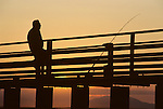 Sunset with older man silhouetted fishing off pier Shilshole Marina with Olympic mountains Seattle Washington State USA