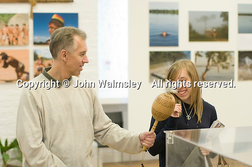 "A father & daughter have fun in the exhibition, ""Heart of Brazil"" by Sue Cunninham. Open Day at Kingston College when prospective students and their parents look around."