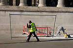 Workman carries construction fencing panel past bending maintenance man in Trafalgar Square.