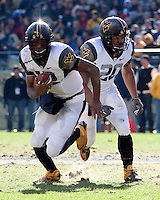 WVU quarterback Geno Smith (left) takes off on a run while running back Shawne Alston (20) looks on. The WVU Mountaineers defeated the Pitt Panthers 35-10 at Heinz Field, Pittsburgh, Pennsylvania on November 26, 2010.