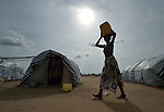 A woman carries water through a camp for almost 500 internally displaced people located at the St. Vincent de Paul Catholic parish on the edge of Juba, the capital of South Sudan. The families here fled fighting that broke out in December 2013. More than 700,000 people have been internally displaced in the first three months. Safe water for the camp is being provided by Norwegian Church Aid, a member of the ACT Alliance.