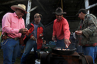 """Taking a break from their work of branding, innoculating, tagging and castrating calves at Kahua Ranch in North Kohala, Hawaii, from left, Godfrey Kainoa, Kimo Ho'opai, Wayne Tachera and Keoki Kainoa clean and prepare """"Laho"""" (calf testicles) for breakfast.  These are cooked with garlic salt and oil directly over the branding fire."""