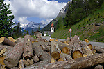 Timber logs strewn on side of road, with background of church and alps. Village Pfaflar on the Hahntennjoch pass, Imst district,Tyrol, Tirol, Austria