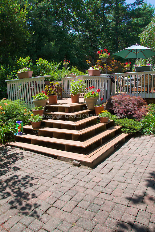 Garden patio of stone pavers with raised wooden deck and stairs