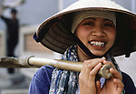 Woman construction worker shoulders a pick axe in Hanoi, North Vietnam.  (Jim Bryant Photo)....