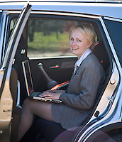 Happy Smiling Businesswoman With Laptop Computer Sitting in Car
