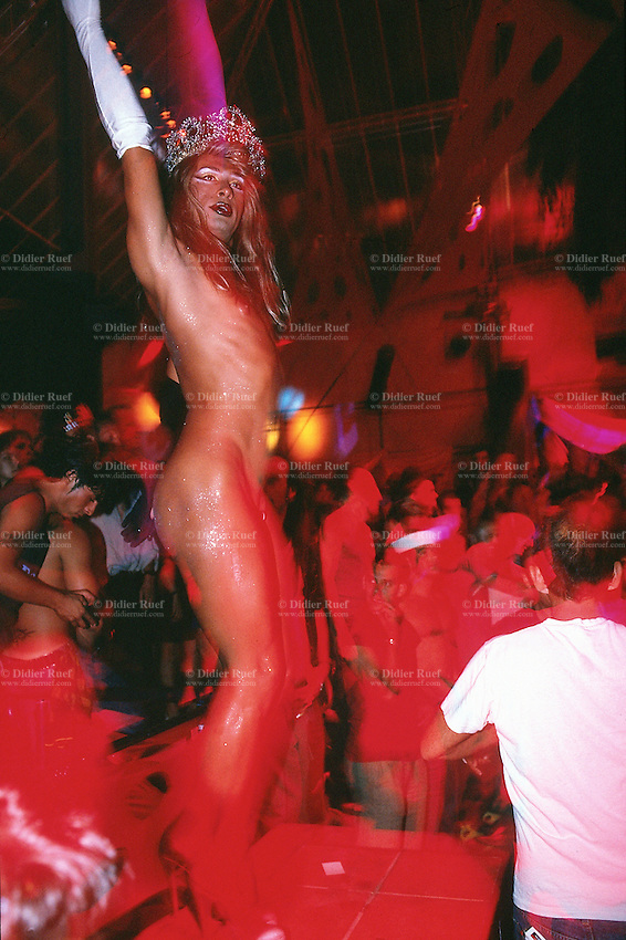 Spain. Ibiza in the Balearic islands. Ibiza. Night life. Amnesia Disco. A sexy young man dances on the sound of the techno music. He is fully naked with just a mirror to hide his penis. He wears a queen's crown on his headand, a white glove on the right arm and hand, a black glove on the left arm and hand. Transsexualism is a condition in which an individual identifies with a physical sex that is different from their biological one. © 1999 Didier Ruef