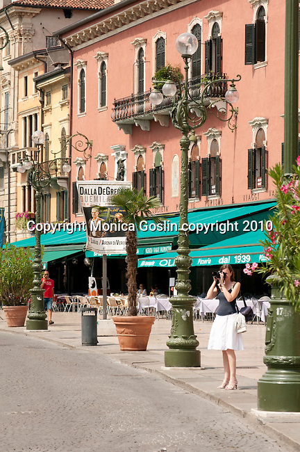 A tourist taking photos in Piazza Bra in Verona, Italy. A woman in a white skirt and navy blue top, stops to take pictures in Piazza Bra in Verona, Italy.