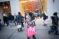 "A shopper with their Victoria's Secret shopping bag in Herald Square in New York on the day after Thanksgiving, Black Friday, November 28, 2014. Many retailers, including Macy's, opened their doors on Thanksgiving evening extending the shopping day and giving Thanksgiving the nickname ""Gray Thursday"". (© Richard B. Levine)"