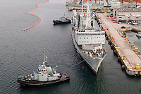 Navy Supply ship being pulled away from dock in Halifax Harbour Nova Scotia Canada North America