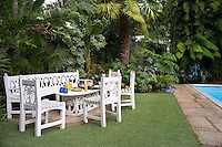 Wooden garden furniture with hand-carved palm tree motifs create an informal outdoor dining area next to the pool