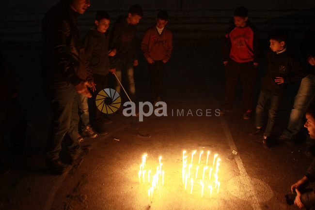Palestinian supporters of Fatah movement place candles during a rally on the eve of the 48th anniversary of the formation on the Fatah movement, on December 31, 2012, in the West Bank city of Nablus. The Fatah anniversary commemorates the first operation against Israel claimed by its armed wing then known as Al-Assifa (The Thunderstorm in Arabic) on January 1, 1965 . Photo by Nedal Eshtayah