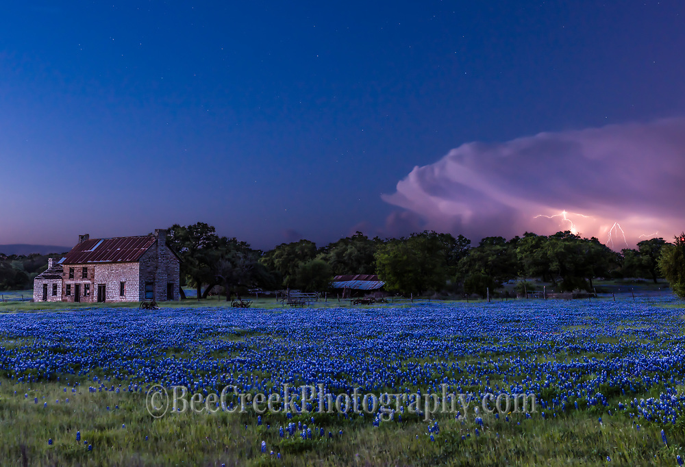 We capture this lightning strike from this storm cloud as we were out taking photos of the bluebonnets at this old farm house in the Texas Hill country. After the sun went down we noticed some lightning in a storm cloud so we hung around to try to capture this image.   We were delighted that we were able to capture it using a composite of two images taken a little earlier before the lightnign strike over this field of bluebonnets. This storm was probably 60 miles away at the time.