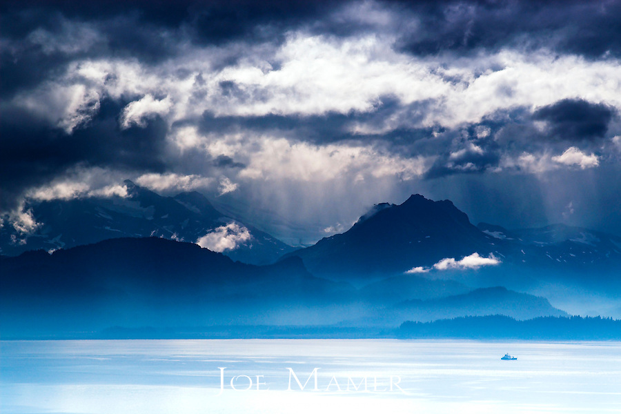 Fishing boat on Kachemak Bay near Homer, Alaska heads for open waters as rain clouds clear over the mountains.