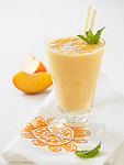 Fresh peach smoothie with straws and fresh mint