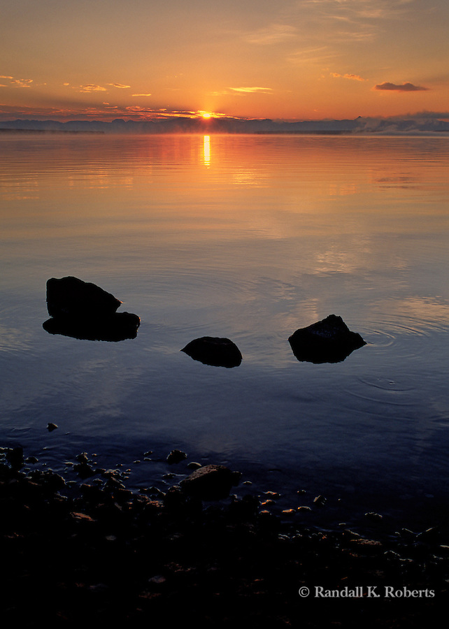 The sun sets casts warm orange light on Yellowstone Lake, Yellowstone National Park, Wyoming