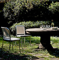 A pair of aluminium chairs stand next to a round stone table at the bottom of this garden