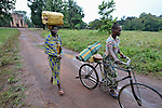 Two women in Riimenze, a village in Southern Sudan's Western Equatoria State, carry water home from a well--one on her head and one on a bicycle. In the background is the village's Catholic church.