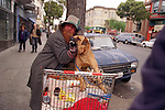 Garland holds his dog off from attacking another male dog that walks close to his shopping cart on Haight and Ashbury Street in San Francisco, California.