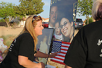 """Gilbert, Arizona – Friends and family of the Mederos Family gathered to hold a memorial for the four victims of the Gilbert Massacre occurred on May 2, 2012. According to Gilbert Police, Lisa Mederos, Amber Mederos, baby Lilly Mederos, and Jim Hiott (Amber's fiancé) were all killed by notorious white supremacist and Neo-Nazi Jason """"J.T."""" Ready before taking his own life. In this image, Mistie Whiteman places an American flag below a picture of victims Lisa Mederos (bottom left picture), Amber Mederos, baby Lilly Mederos and Jim Hiott (photographed together in large picture). Photo by Eduardo Barraza © 2012"""