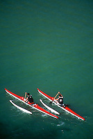 Two kayaks racing in open water under the Burrard Bridge, English Bay, Vancouver, BC.