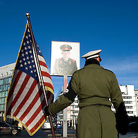 An actor wearing an American soldier's uniform holding a US flag in front of a photo of a Russian soldier at the Berlin Wall's Checkpoint Charlie in Berlin-Mitte.