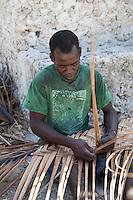 Jambiani, Zanzibar, Tanzania.  Man Weaving a Mat out of Palm Fronds.