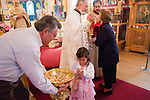 Liturgy service at St. Sava Orthodox Church, Jackson, Calif...Father Stephen Tumbas  assisted by Dan Stojanovich present the sacrament to the prepared faithful at the end of the worship service as a little girl take bread representing the Body of Christ.