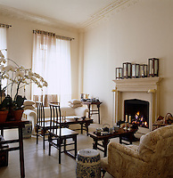 Chinese rosewood chairs and benches face the fire in this well appointed, neutral, drawing room