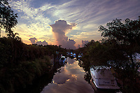 A dissipating thunderstorm reflects from the tranquil surface of a canal shortly after sunrise in Coral Gables, Florida.