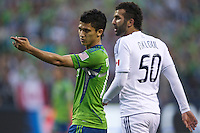 Seattle Sounders FC forward Fredy Montero appeals to the referee during play against the Vancouver Whitecaps FC at Qwest Field in Seattle Saturday June 11, 2011. At right is Vancouver Whitecaps FC  defender Davide Chiumiento. The game ended in a 2-2 draw.