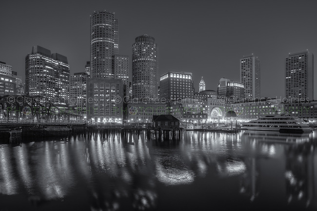 The skyline reflects off the still waters of the harbor in the last hour before sunrise as a new day begins in Boston, Massachusetts.