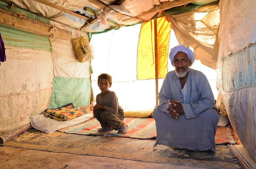 Farag Younis, a Bedouin shepherd, inside his tent with grandson - in the desert outside of Marsa Matruh, Egypt