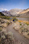 Man hiking along Convict Lake, with early morning light on Laurel Mountain, fall, Inyo National Forest, California