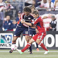 New England Revolution substitute midfielder Juan Toja (18) and Chicago Fire midfielder Logan Pause (12) battle for the ball. In a Major League Soccer (MLS) match, the New England Revolution (blue) defeated Chicago Fire (red), 1-0, at Gillette Stadium on October 20, 2012.