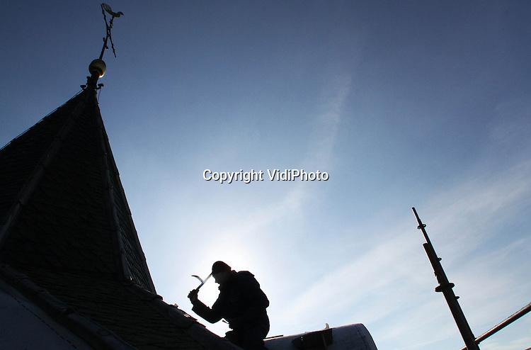 Foto: VidiPhoto..DODEWAARD - Een werknemer van leidekkersbedrijf Engelberts uit Sleeuwijk vernieuwt woensdag de leien bij de torenspits van Hervormde kerk in Dodewaard. In opdracht van de gemeente Neder-Betuwe, die verantwoordelijk is voor de kerktoren, worden de komende weken zo'n 3500 leien vervangen en de dakkapellen aan alle zijden van de toren aangepakt. Die laatste werkzaamheden worden verricht door Bouwbedrijf Woudenberg uit Ameide, die ook het voegwerk doet. De bijzonder gevormde leien (Oud-Duitse dekking) komen uit Duitsland en zijn specifiek voor protestantse kerken. Vrijwel alle RK-kerken gebruiken Als het weer mee werkt, zijn de werkzaamheden aan de kerktoren langs de Waaldijk -een van de oudste kerktorens van ons land- voor eind november gereed. De kosten van ruim een ton komen voor rekening van gemeente Neder-Betuwe en Rijk (subsidie)..
