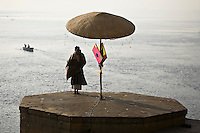 A pilgrim watches life along the holy river Ganges, an important pilgrimage site for Hindus, in Varanasi, Uttar Pradesh, India.<br /> (Photo by Matt Considine - Images of Asia Collection)