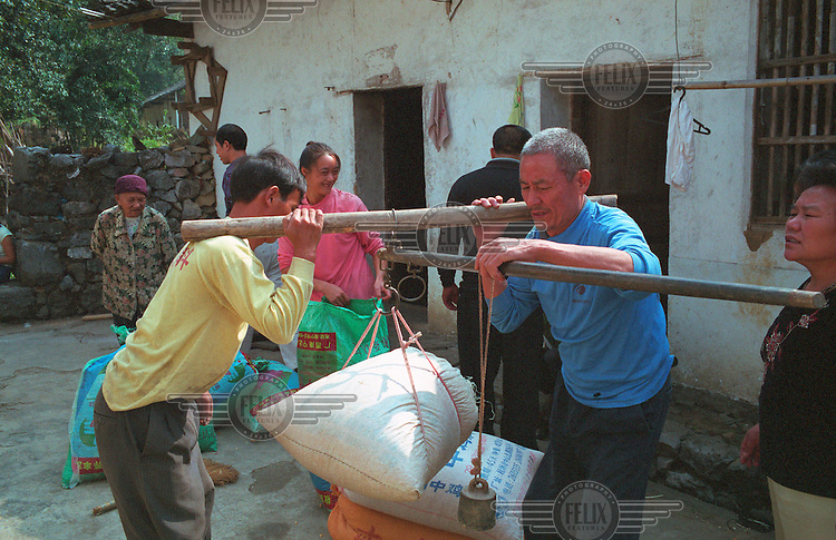Villagers weigh their corn harvest with a grain collector in Yongle.