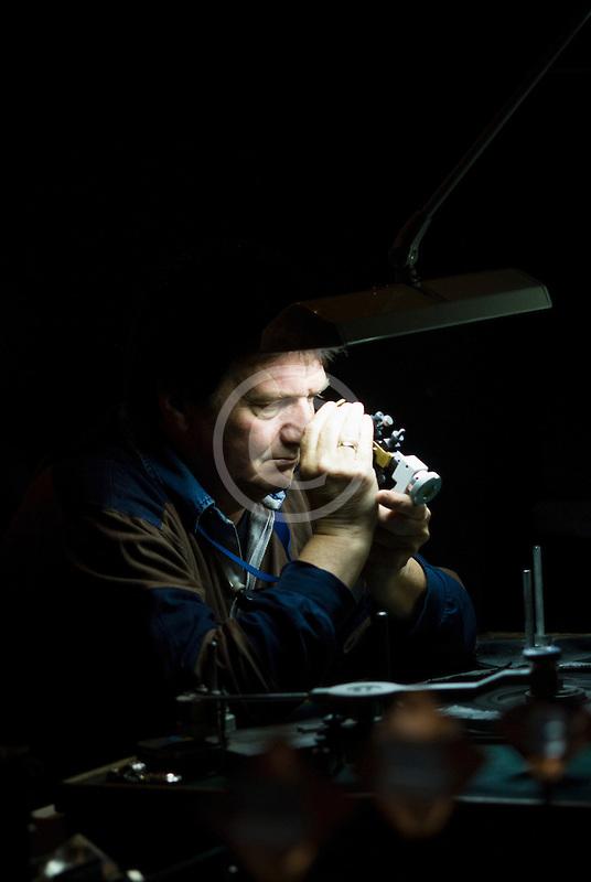 Belgium, Antwerp, Jeweler examining a diamond at the Diamond Museum