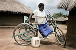PAICHO, UGANDA AUGUST 3: Akumu Nighty, age 20, a victims of the civil war, climbs on her cycle outside her hut on August 3, 2005 in Paicho, a camp for displaced people in Northern Uganda. She was injured by the Lord's Resistance Army (LRA) and was later taken to hospital in Gulu, the provincial capital. The rebel group has brought terror to Northern Uganda for almost twenty years, fighting the Ugandan government. The victims are usually children, which are abducted and used as child soldiers and sex slaves. Many of the abducted children are forced to perform gruesome acts and are usually brainwashed when initiated in the LRA. About 60.000 people live in the camp in bad conditions. (Photo: Per-Anders Pettersson)....